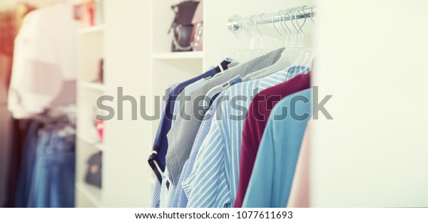 Fashion. In the women's clothing store. Shopping center. Small business, shop. Hanger with a new collection of dresses. Place for text.