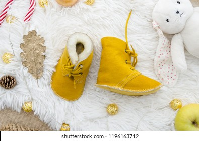 Fashion yellow genuine leather soft natural kids shoes.Newborn hand made real sheepskin Baby Slippers. Autumn winter concept flat lay