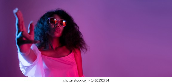 Fashion young african girl black woman wear stylish pink glasses dance look at camera shoot hand gun isolated on party disco purple studio background, banner for website design, portrait, copy space