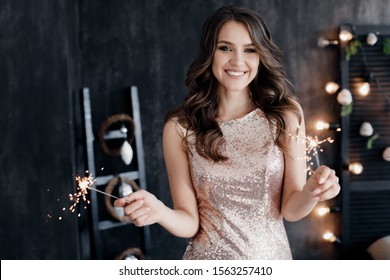 Fashion young beautiful woman in knitted dress near christmas tree. Fashion beautiful sensual new year woman with makeup in luxurious interior