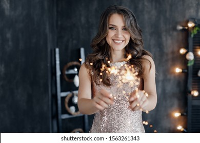 Fashion young beautiful woman in luxury dress and makeup. christmas and new year. girl with sparlight lights