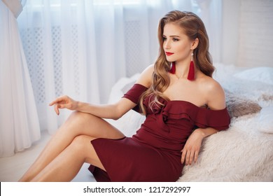Fashion young beautiful woman in red short dress sitting in antique armchair. Fashion beautiful sensual blond woman with makeup in luxurious prom dress