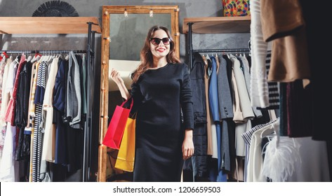 Fashion young brunette hair girl wearing sunglasses enjoying her shopping weekend in the shopping center, black friday concept
