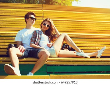 Fashion young couple teenagers are resting in the city park on the bench at summer sunny day