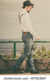 Fashion. Young fashionable man retro style wearing denim pants with straps black hat on outdoor