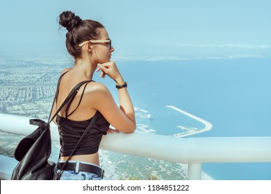 Fashion young girl with backpack in casual clothes glasses enjoying a view from the mountain to the sea. Tourist traveler standing on viewing platform of hotel agaist blue background valley landscape