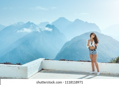 Fashion young girl in casual clothes sunglasses enjoying sunset on peak of mountain. Tourist traveler sitting on viewing platform of hotel agaist blue background valley landscape view mockup for text