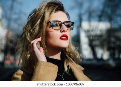 Fashion young girl in glasses. Blonde, red lips, beige coat walking along the city street. Fashion, stylish girl with a hipster hairdo. Creative person.