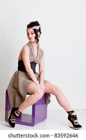 Fashion young girl sitting on modern chair in studio