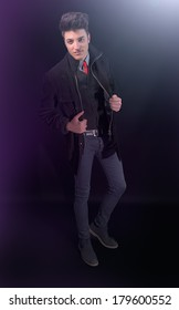 Fashion young man in jeans and jacket on black background