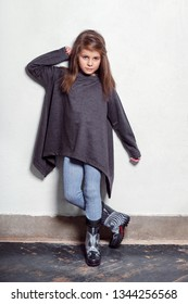 Fashion young model kid posing in a stylish, urban, casual clothes. Little child looks with a serious, hand touching her hair, standing near white wall. children's leggings, sweater, rubber boots..