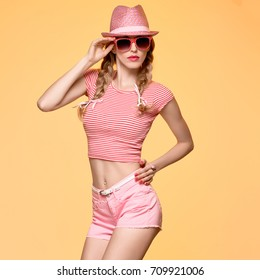 Fashion. Young Playful Hipster Having Fun Crazy in Trendy Pink Summer Hat. Beautiful Woman in Stylish Outfit. Cool Blond Model Girl in Sunglasses, Shorts on Yellow background