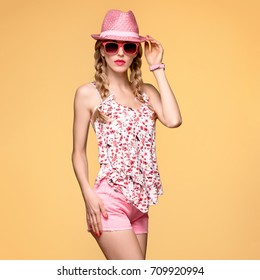Fashion. Young Playful Pretty Hipster in Trendy Pink Summer Hat. Beautiful Woman in Stylish Outfit. Blond Model Girl in Sunglasses, Shorts on background