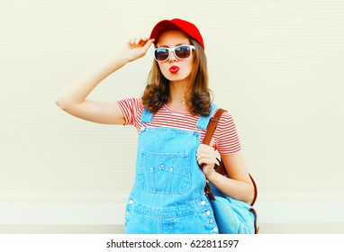 Fashion young pretty woman wearing a denim jumpsuit with baseball cap and sunglasses over white background