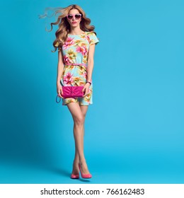 Fashion Young shapely woman in Floral Dress. Glamour Sexy Blond Model. Trendy, Stylish wavy Hairstyle, fashionable Sunglasses, Heels. Magnificent Summer Girl with long hair on Blue, full-length