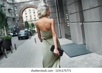 Fashion. Young stylish woman walking on the city street back view windy weather