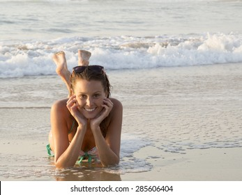 fashion young woman in bikini and sunglasses lying on beach, with wet hair