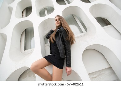 Fashion young woman in a black rock on a white wall background