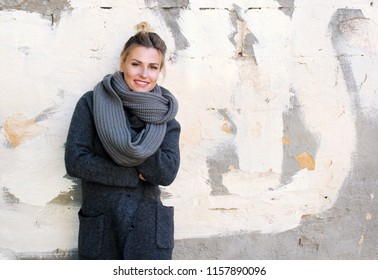 fashion. a young woman in a coat, a sweater and a fashionable scarf stands near the wall