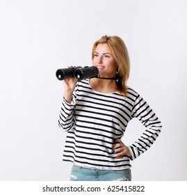 Fashion. Young woman in fashionable sweater is holding binoculars in hands on a white background