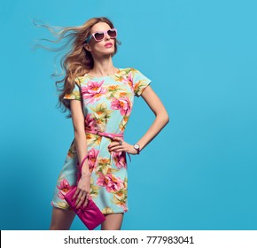 Fashion Young woman in Floral Dress. Trendy wavy Hairstyle. Glamour Sexy Blond Model, Stylish Sunglasses, fashionable Clutch. Playful Summer Girl on Blue