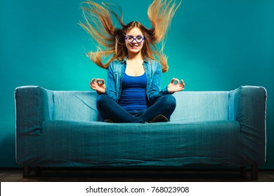 Fashion young woman in full length. Fashionable girl wearing denim sitting on couch wind in hair blue background