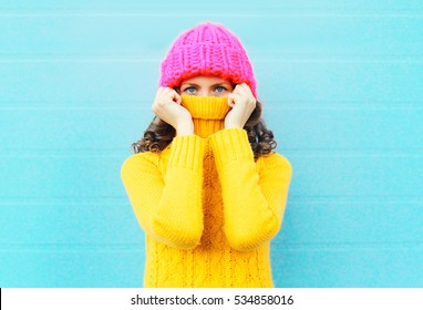 Fashion young woman hide face wearing a knitted pink hat yellow sweater over blue background