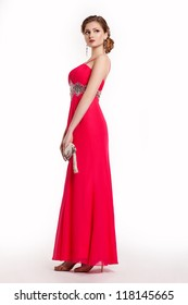 Fashion young woman in luxury red long dress with handbag posing. Formal party