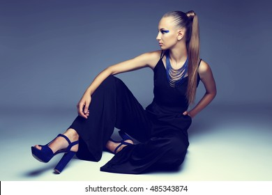 Fashion young woman. Fashion makeup, black overall, necklace, pony tail blond hair.