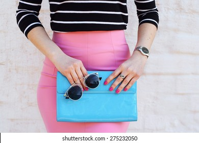 Fashion young woman in pink skirt and black blouse with blue clutch , accessories, watch and sunglasses white background