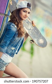 Fashion young woman posing with a skateboard