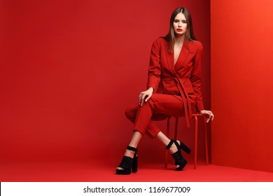 Fashion young woman in red suit. Red background.