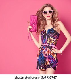 Fashion Young woman in Trendy Spring Summer Dress. Stylish wavy hairstyle, Sunglasses, Floral Outfit. Glamour Blond lady in fashionable Jumpsuit. Playful Girl, Luxury Pink Clutch