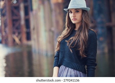Fashion young woman wearing hat at riverside