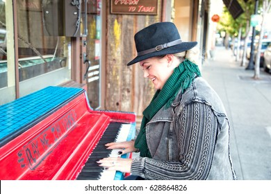 A fashionable, 30-something woman plays piano on a city street