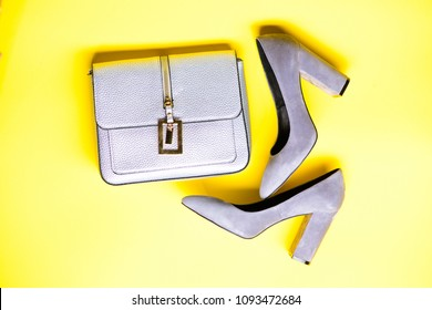Fashionable accessories concept. Footwear for women with thick high heels and bag, top view. Pair of fashionable high heeled shoes and silver purse. Shoes made out of grey suede on yellow background