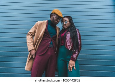 fashionable african american couple in jacket and overcoat posing together outside