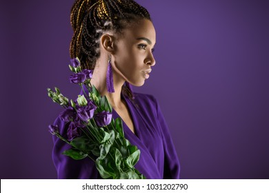Fashionable african american girl posing with purple eustoma flowers, isolated on purple, ultra violet trend