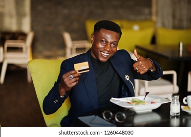 Fashionable african american man in suit sitting at cafe with credit card in his hand and show thumb up.
