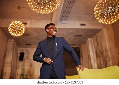 Fashionable african american man in suit and glasses posed at cafe.