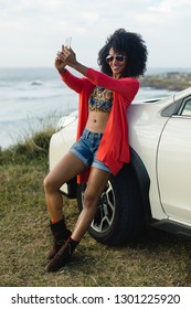 Fashionable afro hair woman on vacation taking selfie photo with smartphone towards the sea. Stylish black model enjopying a car trip to the coast.