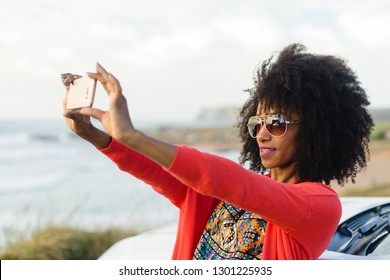 Fashionable afro hair woman on vacation taking selfie photo with smartphone towards the sea. Stylish black model on a car trip to the coast.