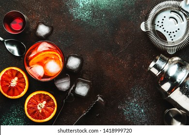 Fashionable alcoholic cocktail Negroni with dry gin, red vermouth and red bitter, orange and ice cubes. Brown bar counter background, bar tools, top view, place for text.