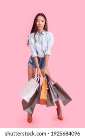 Fashionable Asian woman carrying pastel colored shopping bags. High fashion model isolated over pink background concept.