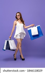 Fashionable Asian woman carrying shopping bags and walking on purple isolated studio background