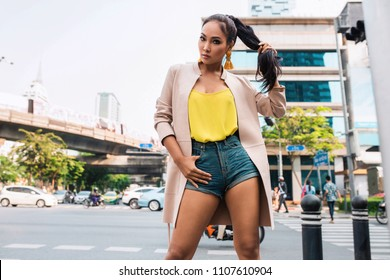 Fashionable Asian woman in short jeans and nice clothes, yellow top walking in the street. Fashion spring summer autumn photo