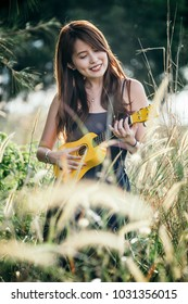 Fashionable attractive Chinese female with dimple, curly brown hairs, strumming a yellow ukulele with backlit sun.