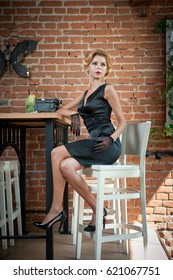 Fashionable attractive lady with little black dress and long gloves standing near a restaurant table having a drink. Short hair blonde woman with makeup and creative haircut holding a glass with fresh
