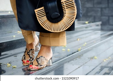 Fashionable bag close-up in female hands.Girl walks in the city outdoors. Stylish modern and feminine image, style. Woman in a dress and beige trousers, holds a straw bag. Snake shoes or sandals