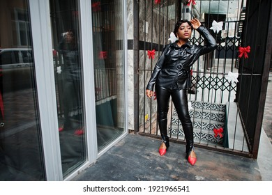 Fashionable beautiful african american woman posing in black leather jacket and pants at street.
